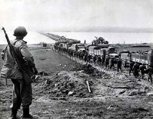 <p>German prisoners file across the Rhine as American supply trucks move forward toward the front. March 26, 1945. US Army Signal Corps photograph.</p>