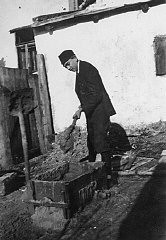 """<p><a href=""""/narrative/5696/en"""">Naftali Saleschutz</a> (Norman Salsitz) prepares cement for the foundation of a sukkah (a hut-like structure used to celebrate the Jewish holiday of Sukkot). Kolbuszowa, Poland, 1937.</p>"""