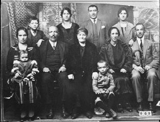 """<p>Portrait of an unidentified family of eight adults and three children in Bitola.</p> <p>This photograph was one of the individual and family portraits of members of the <a href=""""/narrative/9092/en"""">Jewish community of Bitola</a>, Macedonia, used by <a href=""""/narrative/5955/en"""">Bulgarian occupation authorities</a> to register the Jewish population prior to its deportation in March 1943.</p>"""