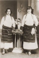 """<p>Portrait of two Jewish girls dressed in traditional Macedonian costume in a private home in Bitola. Pictured are Matilda Kamchi (or Camhi, left) and a friend. Both perished in <a href=""""/narrative/3819/en"""">Treblinka</a>. Bitola, 1937.</p>"""