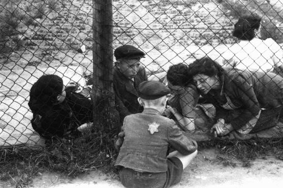 """<p>Family members say goodbye to a <a href=""""/narrative/2562/en"""">child</a> through a fence at the ghetto's central prison where children, the sick, and the elderly were held before deportation to Chelmno during the """"Gehsperre"""" action. Lodz, Poland, September 1942.</p>"""