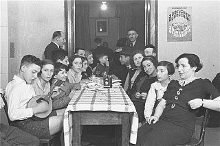 """<p>Members of the Chug Ivri (Hebrew Club) in Berlin celebrate <a href=""""/narrative/9164/en"""">Purim</a> with food and song. On the wall is an advertisement for <em>Juedische Rundschau</em>, the newspaper of the German Zionist movement. Berlin, Germany, 1935.</p>"""