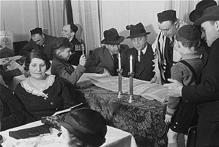 """<p>Members of Chug Ivri (Hebrew Club) of Berlin celebrate Purim. While the man in the tallis (prayer shawl) chants the story of <a href=""""/narrative/9164/en"""">Purim</a> from the scroll, a young boy stands ready to use his grogger (noisemaker) to drown out the recitation of the name of Haman, the villain of the story. Berlin, Germany, 1935.</p>"""