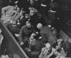 "<p>The defendants' box at the Nuremberg trial. <a href=""/narrative/11329/en"">Hermann Göring</a> is seated at the far left of the first row. Nuremberg, Germany, 1945-1946.</p>"