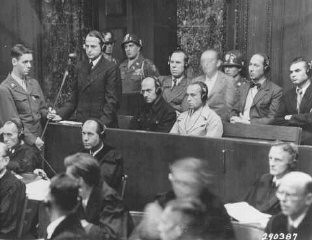 "<p>Otto Ohlendorf, commander of Einsatzgruppe D (mobile killing unit D), during Trial 9 of the Subsequent Nuremberg Proceedings. This photograph shows Ohlendorf pleading ""not guilty"" during his arraignment at the <a href=""/narrative/9545/en"">Einsatzgruppen Trial</a>. Nuremberg, Germany, September 15, 1947.</p>"