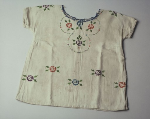 <p>A child's dress embroidered with red and blue flowers with small green leaves. This dress was hand embroidered by Lola Kaufman's mother in the Czortkow ghetto. Lola (born Lea Rein) wore this dress when she went into hiding. Lola was hidden first under a bed in the house of the woman who used to deliver milk to the family, then in a dugout under a cellar of a barn where she joined three other Jews in hiding. In March 1944, the Soviets liberated the area. The hidden Jews left their hideout in the middle of the night. Eight-year-old Lola joined a crowd of refugees walking eastwards.</p>