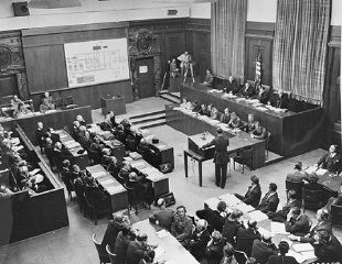 "<p>US Chief of Counsel Brigadier General Telford Taylor (standing at center podium) opens the prosecution's case at the <a href=""/narrative/9506/en"">IG Farben Trial</a>. Note the camera in the corner of the room. August 27, 1947.</p>"