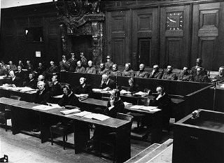 "<p>The defendants in the dock (at rear, with headphones) and their lawyers (front) follow the proceedings of the <a href=""/narrative/9521/en"">Hostage Case</a>, case #7 of the <a href=""/narrative/9461/en"">Subsequent Nuremberg Proceedings</a>. Nuremberg, Germany, 1947-48.</p>"