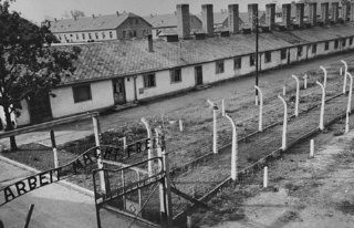 "<p>View of the kitchen barracks, the electrified fence, and the gate at the main camp of Auschwitz (Auschwitz I). In the foreground is the sign ""Arbeit Macht Frei."" This photograph was taken after the liberation of the camp by Soviet forces. Auschwitz, Poland, 1945.</p>"