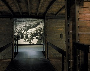 <p>View of the photo mural of a selection at Auschwitz-Birkenau taken through the open railcar on the third floor of the Permanent Exhibition at the United States Holocaust Memorial Museum. Washington, DC, 1993–95.</p>
