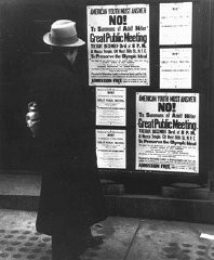 "<p>A pedestrian reads a notice announcing an upcoming public meeting, scheduled for Tuesday, December 3, to urge Americans to boycott the upcoming <a href=""/narrative/7139/en"">1936 Berlin Olympics</a>. New York, United States, 1935.</p>"