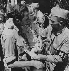 <p>American military police admit a father and daughter, both displaced persons, to the refugee shelter at Fort Ontario. Oswego, New York, United States, after August 4, 1944.</p>