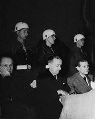 "<p>Defendants <a href=""/narrative/9811/en"">Karl Dönitz</a> (left), <a href=""/narrative/9877/en"">Erich Raeder</a> (center), and <a href=""/narrative/9908/en"">Baldur von Schirach</a> under guard in the defendants' dock at Nuremberg.</p>"
