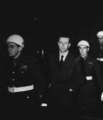 "<p>Defendant <a href=""/narrative/9828/en"">Hans Fritzsche</a> enters the Nuremberg courtroom under American guard during the International Military Tribunal.</p>"
