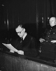 "<p>Defendant <a href=""/narrative/9881/en"">Alfred Rosenberg</a>, the former chief Nazi Party ideologist, reads a document during the <a href=""/narrative/9366/en"">International Military Tribunal</a> trial of war criminals at Nuremberg. Behind him is his co-defendant General <a href=""/narrative/9852/en"">Alfred Jodl</a>, formerly the Chief of Staff for the Army. Nuremberg, Germany, 1945–1946.</p>"