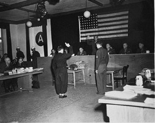 <p>A witness is sworn in at the trial of 61 former personnel and prisoners from the Mauthausen concentration camp. Swearing him in is Major General Fay Brink Prickett, the president of the Military Tribunal. March 29 - May 13, 1946.</p>