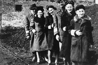 """<p>Young Jewish men and women post for a photograph in the Piotrkow Trybunalski ghetto. Poland, 1940.</p> <p>Pictured from left to right are: Abram Zarnowiecki, Rozia Zarnowiecki, Mania Freiberger, Moniek, Rachel Zarnowiecki, and Chaim Zarnowiecki.</p> <p>All those pictured died in the <a href=""""/narrative/72/en"""">Holocaust</a>.</p>"""