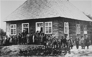 <p>Prewar group portrait in front of a synagogue in the Transylvanian town of Sighet.</p>