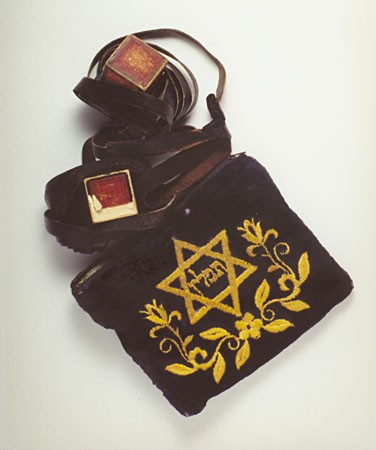 <p>Set of tefillin in an embroidered bag. Tefillin are ritual objects worn by religious Jews during weekday morning prayers. This set was found on the body of a death march victim, who was buried near Regensburg, Germany.</p>