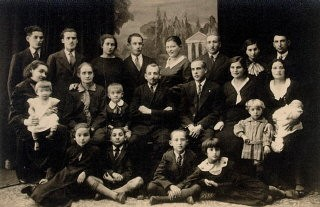 """<p>Portrait of Aron's family on his mother's side, taken when Aron's cousin moved to Israel in 1933-1934. Aron is seated second from left, bottom row. His mother, Miriam, is in the center row, second from right. Aron's father is behind her and to her right. Aron himself was 8 or 9 years old when this picture was taken in either May or June. At the time, Aron recalled, """"I was thinking about going to summer camp."""" Slonim, Poland, 1933-1934.</p>"""