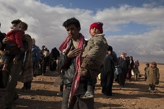 <p>Refugees displaced by the violence in Syria walk to a transit center in Jordan where they will be transported to the Zaatari refugee camp. February 2014.</p>