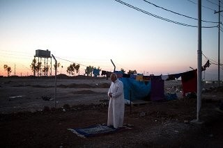 <p>A Sunni man from Mosul, Iraq, prays as the sun sets over an internally displaced persons (IDP) camp near Erbil, Iraqi Kurdistan. September 2, 2015.</p>