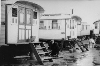 <p>A man works outside his family's dwelling in a Roma (Gypsy) encampment in the city of Haarlem. The Netherlands, October–November 1940.</p>