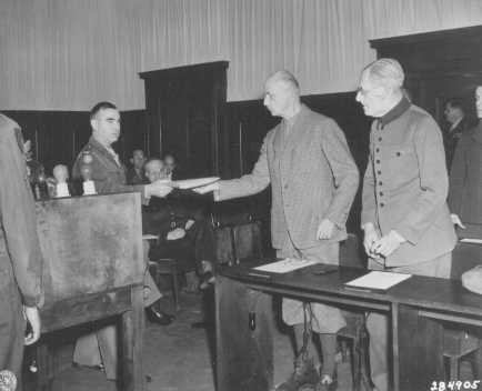 An American soldier serves former German Field Marshal Wilhelm List with his indictment at the beginning of the Hostage Case.