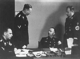 "<p><a href=""/narrative/6141/en"">Heinrich Himmler</a> (seated, center), chief of the SS, with <a href=""/narrative/10812/en"">Reinhard Heydrich</a> (standing, left), chief of the Reich Main Security Office (RSHA). Berlin, Germany, 1938.</p>"