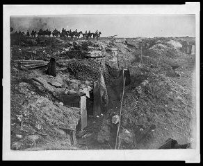 <p>Scene of trench warfare: an abandoned British trench which was captured by German forces during World War I. German soldiers on horseback view the scene.</p>