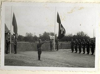 <p>The beginning of a ceremony to dedicate a new SS hospital in Auschwitz-Birkenau. A Nazi soldier salutes as the Nazi and SS flags are raised while a line of troops stand with rifles at attention during the dedication.</p>