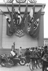 "<p>German spectators at a Nazi rally stand alongside a monument decorated with Nazi flags and a <a href=""/narrative/10948/en"">swastika</a> emblem in Berlin. Germany, 1937.</p>"