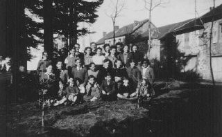 "<p>Group of Jewish children who were sheltered in the children's home Maison des Roches, which was directed by Daniel Trocme (back, center, with glasses). <a href=""/narrative/11043/en"">Le Chambon-sur-Lignon</a>, France, between 1941 and 1943.</p>"