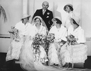 <p>Portrait of Hilde and Gerrit Verdoner, with four bridesmaids, on their wedding day. The bridesmaids are: Jetty Fontijn (far left), Letty Stibbe (second from right), Miepje Slulizer (right), and Fanny Schoenfeld (standing, back). Amsterdam, the Netherlands, December 12, 1933.</p>