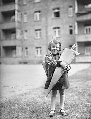 <p>Berta Rosenheim poses with a large cone, traditionally filled with sweets and stationery, on her first day of school. Leipzig, Germany, April 1929.</p>