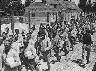 <p>Prisoners carrying bowls in the Dachau concentration camp. Dachau, Germany, between 1933 and 1940.</p>