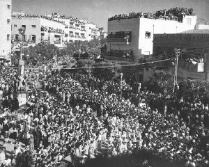 """<p>Crowds gathered in the streets of Tel Aviv celebrate the anniversary of the <a href=""""/narrative/6306/en"""">establishment of Israel</a> with an independence day parade. Tel Aviv, Israel, May 1949.</p>"""