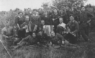 """<p><a href=""""/narrative/5679/en"""">Jewish partisans</a>, including a song and dance group, in the Naroch forest in Belorussia. In addition to armed resistance, Jewish resistance also focused on spiritual resistance—the attempt to preserve traditions and culture. Soviet Union, 1943.</p>"""