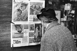 <p>In Berlin, a German woman reads a copy of the Berliner Illustrierte newspaper, featuring photographs of Mussolini's official visit to Berlin in September 1937.</p>
