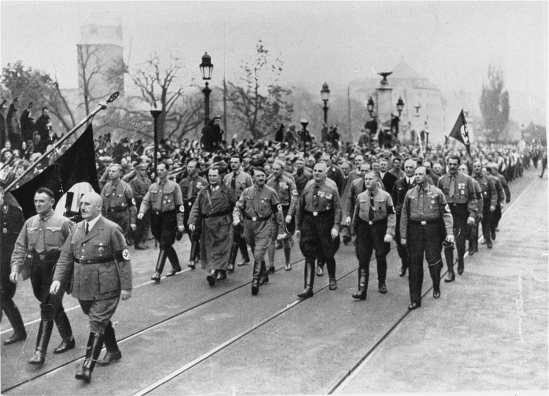 "<p>Adolf Hitler, Julius Streicher (foreground, right), and Hermann Göring (left of Hitler) retrace the steps of the 1923 <a href=""/narrative/11449/en"">Beer Hall Putsch</a> (coup). Munich, Germany, November 9, 1934.</p>"