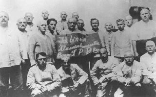 """<p>Humiliation of political prisoners: Social Democratic Party (SPD) inmates hold a placard which reads """"I am a class-conscious person, party boss/SPD/party boss."""" <a href=""""/narrative/4391/en"""">Dachau</a> concentration camp, Germany, between 1933 and 1936.</p>"""