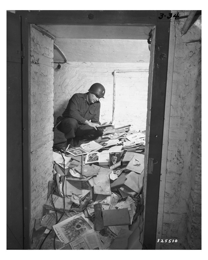 "<p>A US soldier inspects piles of Nazi books, including <em>Mein Kampf</em>, that were found in a German school. As part of their denazification policies, Allied authorities purged German libraries, bookstores, and schools of <a href=""/narrative/81/en"">Nazi propaganda</a>. Aachen, Germany, May 2, 1945.</p>"