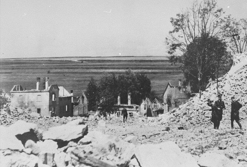 """<p>SS officers stand among the rubble of <a href=""""/narrative/11788/en"""">Lidice</a> during the demolition of the town's ruins in reprisal for the assasination of <a href=""""/narrative/10812/en"""">Reinhard Heydrich</a>. Czechoslovakia, between June 10 and June 30, 1942.</p>"""