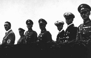 <p>Adolf Hitler stands with his military high command at an inspection of German armed forces. From left to right: Hitler, Hermann Goering, Werner von Blomberg (armed forces), Erich von Fritsch (army) and Erich Raeder (navy). Germany, 1935.</p>