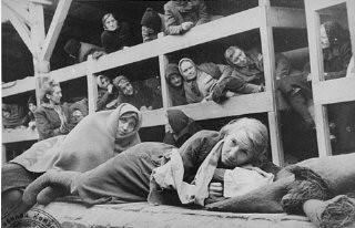 "<p>Women survivors huddled in a prisoner barracks shortly after Soviet forces liberated the <a href=""/narrative/3673/en"">Auschwitz</a> camp. Auschwitz, Poland, 1945.</p>"