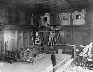 <p>Repairs and improvements are made to the courtroom where the International Military Tribunal trial of war criminals would be held. The holes in the walls at the top (when completed) housed radio commentators and public address operators. September 11, 1945.</p>