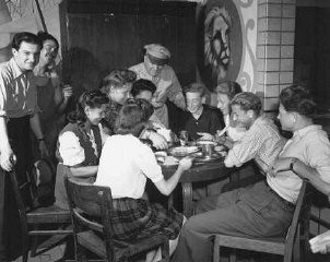 <p>An officer of the United Nations Relief and Rehabilitation Administration (UNRRA) visits with a group of young refugees. Eschwege displaced persons camp, Germany, July 7, 1946.</p>