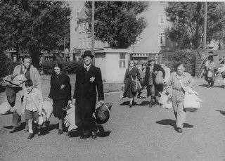 <p>Jews proceed to an assembly point before deportation from Amsterdam. Amsterdam, the Netherlands, June-September 1943.</p>