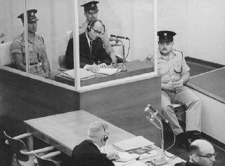 """<p><a href=""""/narrative/3359/en"""">Defendant Adolf Eichmann</a> takes notes during his trial in Jerusalem in 1961.</p>"""