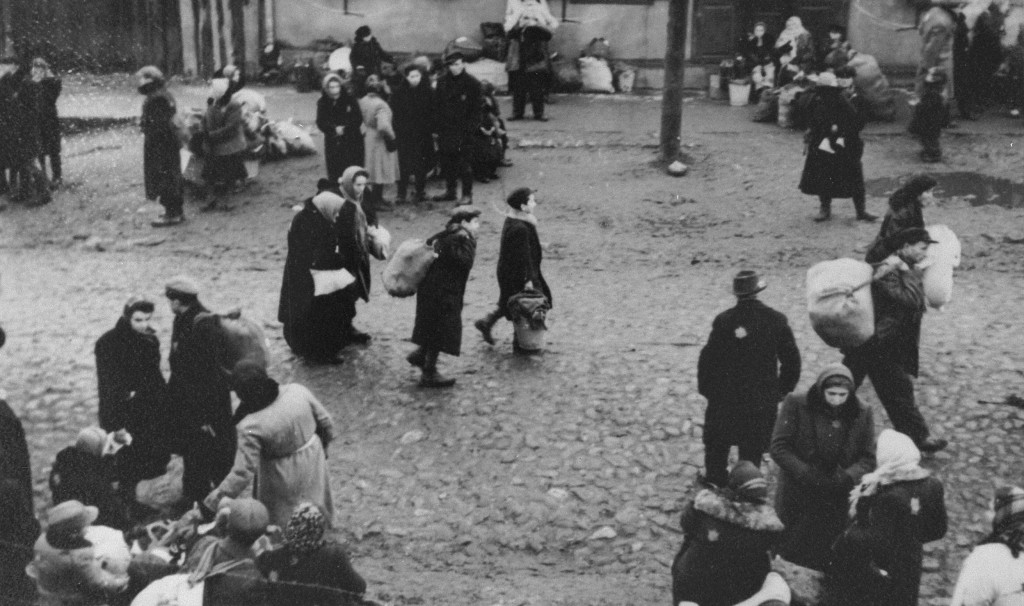 """<p>Jews carrying bundles of possessions who were forced to gather at an assembly point before their deportation from the <a href=""""/narrative/3182/en"""">Kovno ghetto</a>, probably to Estonia. Kovno, Lithuania, October 1943.</p> <p>This photograph was taken by <a href=""""/narrative/11692/en"""">George Kadish</a>.</p>"""